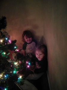 Two of Sonja and my grands hanging out behind our Christmas tree: Rory & Annie God help us to pass on the message behind the tree!